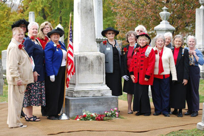 group of members standing near cemetery monument