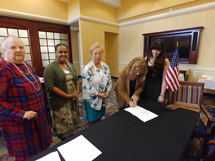 New member application being signed.