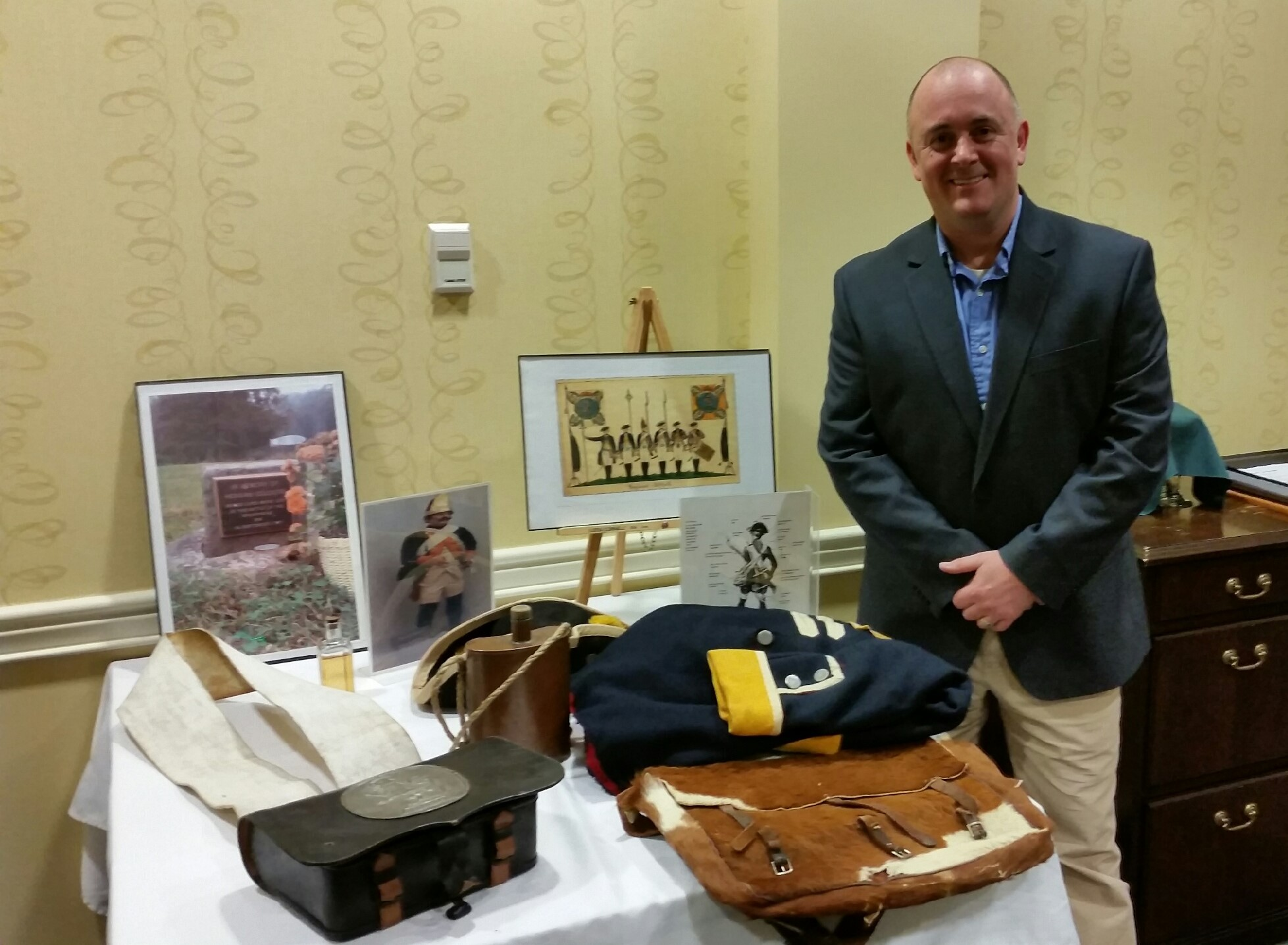 Mike Jesberger stands beside table of historical artifacts