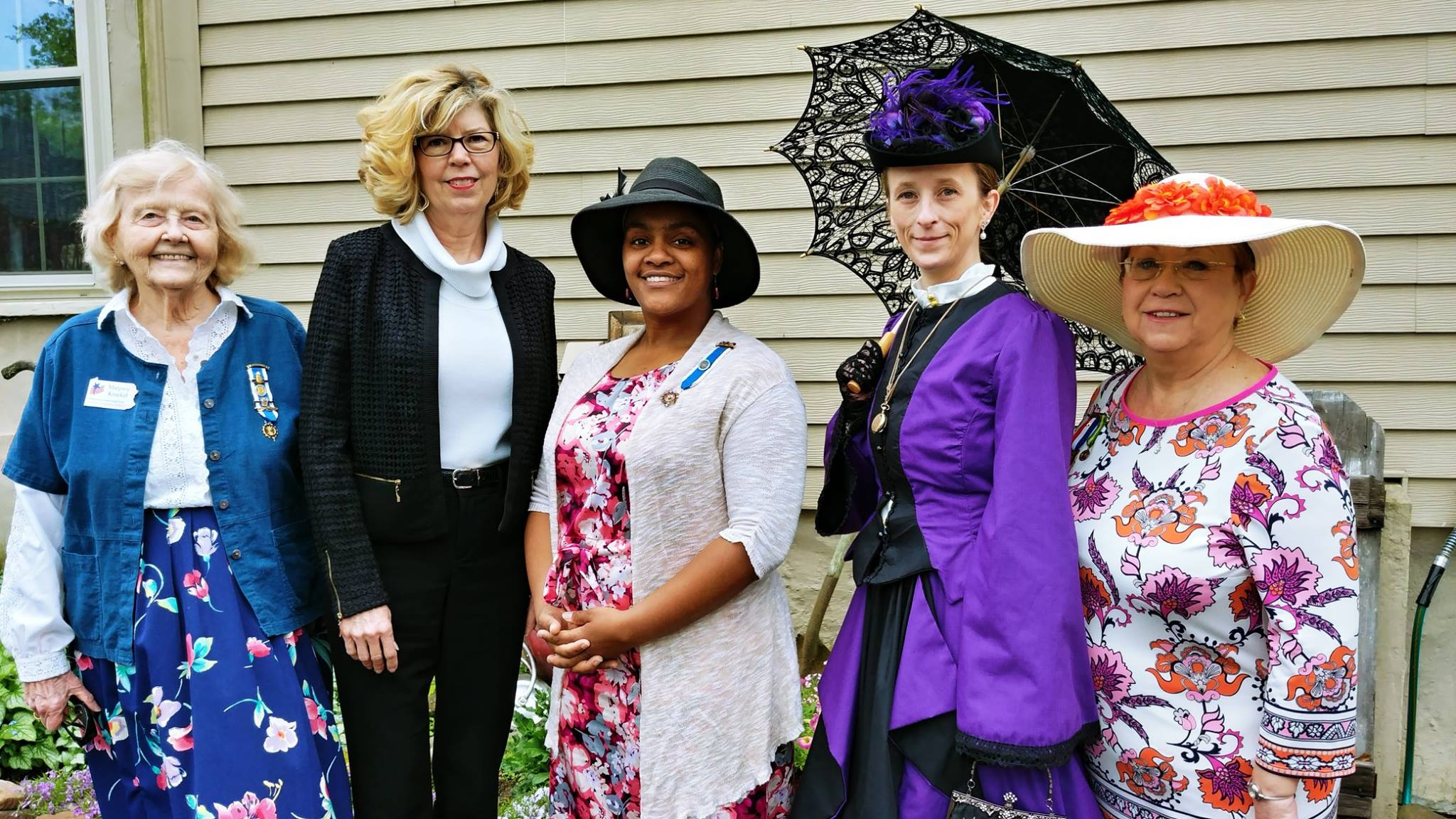 five women wearing fancy hats and attire