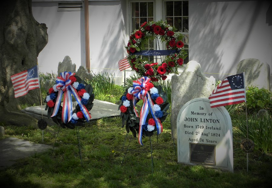 grave with marker surrounded by wreaths and ribbons