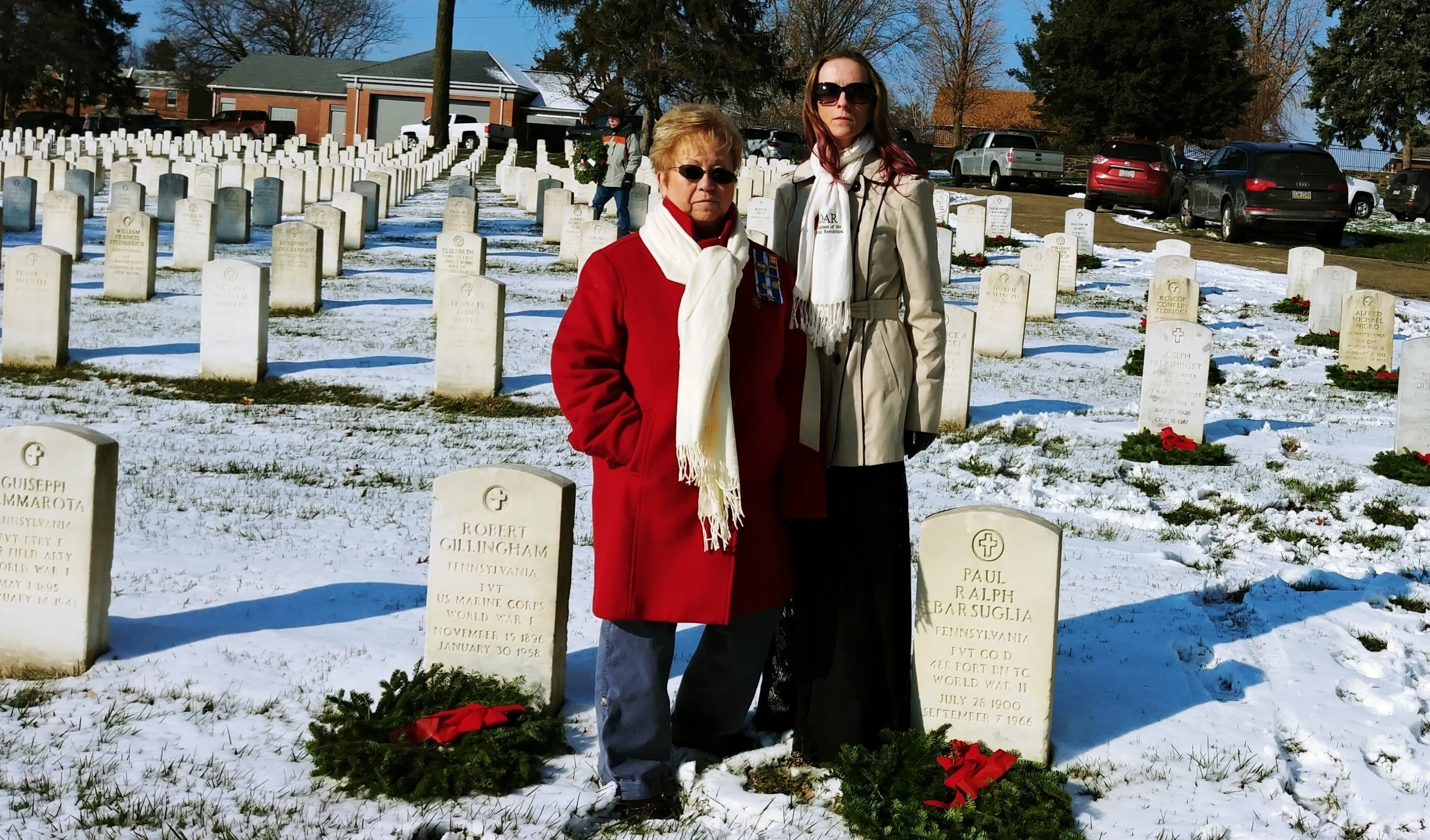 two members standing in cemetery after placing wreaths